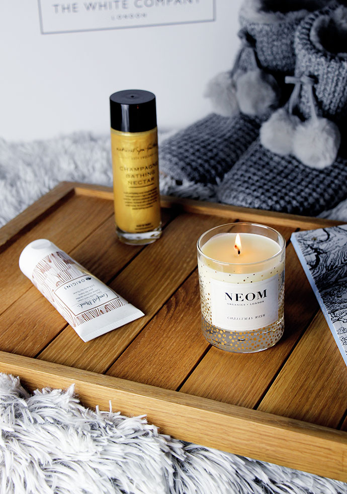 Small Comforts in Knitted Pom Pom Slippers from The White Company, Comfort Mood Origins Vanilla Hand cream, Natural Spa Factory Champagne Bathing Nectar and Neom Organics Christmas Wish Candle by Zoe Newlove